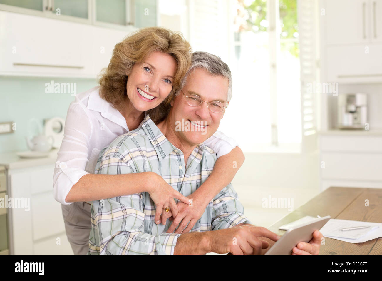 Portrait of smiling senior couple with digital tablet in kitchen - Stock Image
