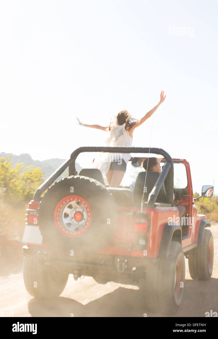 Woman cheering in sport utility vehicle on dirt road - Stock Image