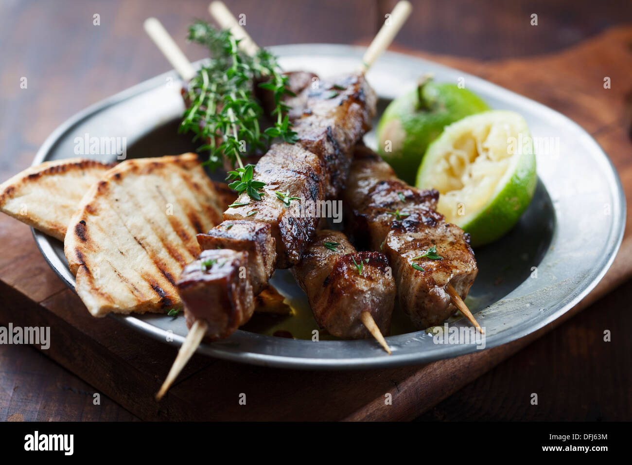 meat skewer with herbs, lime and pita bread - Stock Image