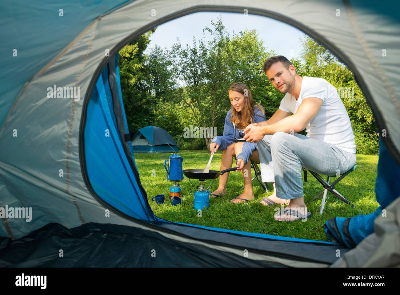 A young couple cooking in front of a tent - Stock Image