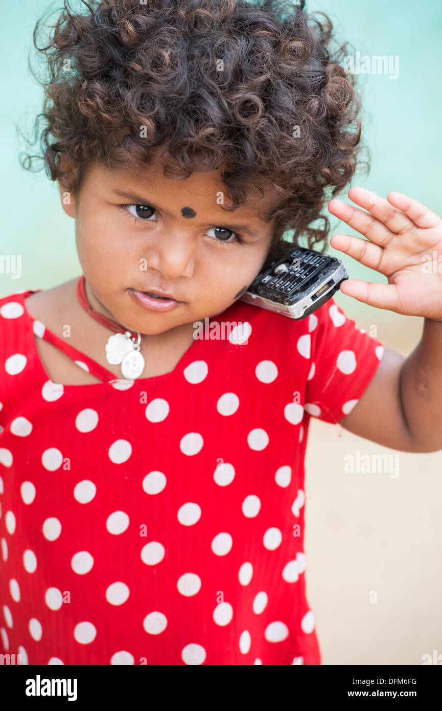 Young Indian girl / infant pretending to use a mobile phone in a rural indian village. Andhra Pradesh, India - Stock Image