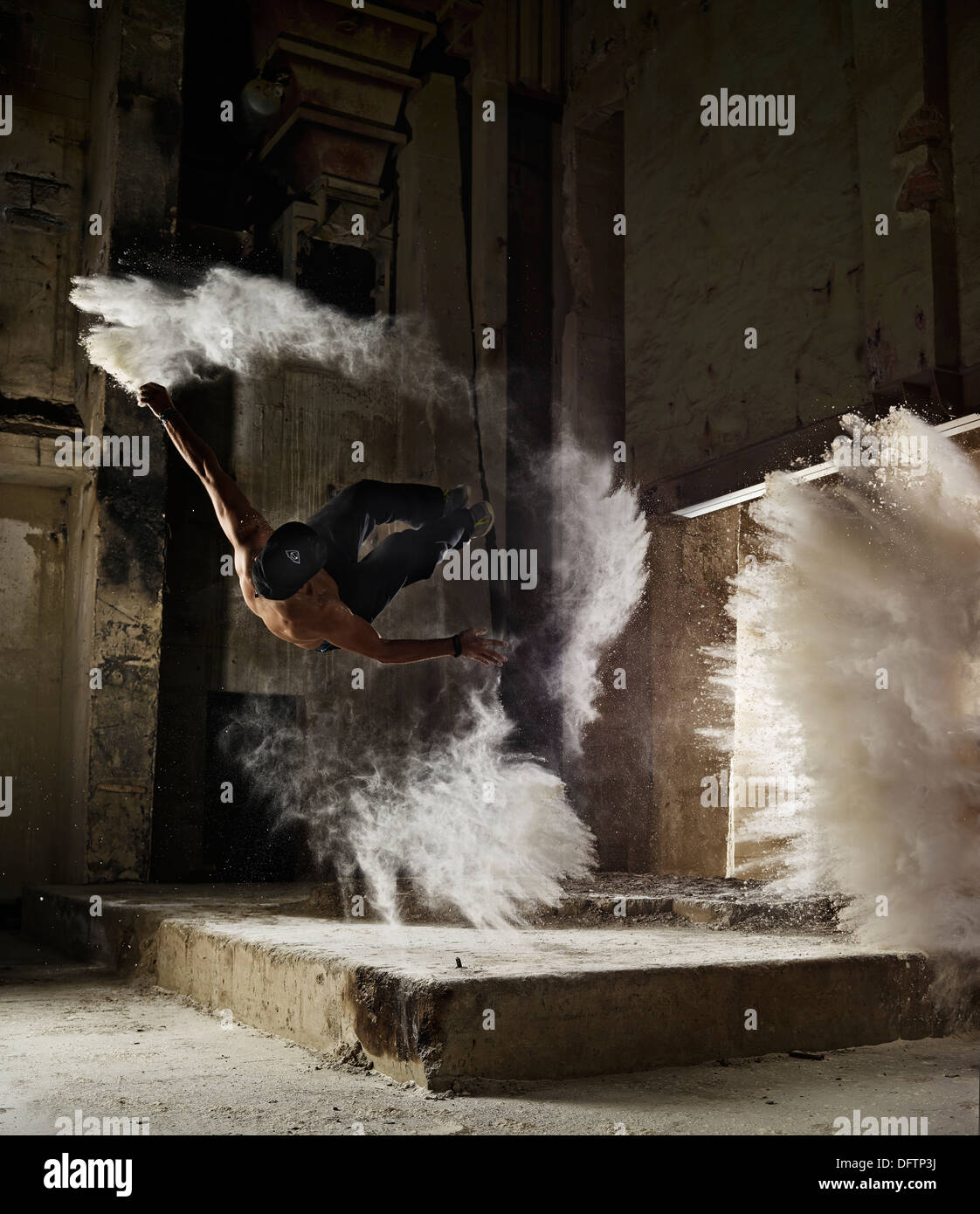 Free Runner performing a Sideflip, with flour dust, Parkour, Bavaria, Germany - Stock Image