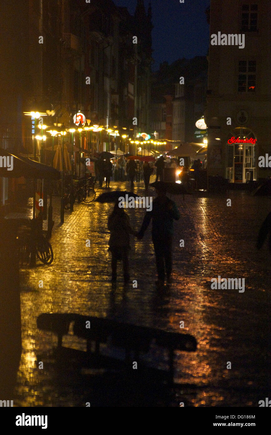 A couple with umbrellas in a rain shower at night  in Heidelberg, Baden-Wurttemberg, Germany Stock Photo