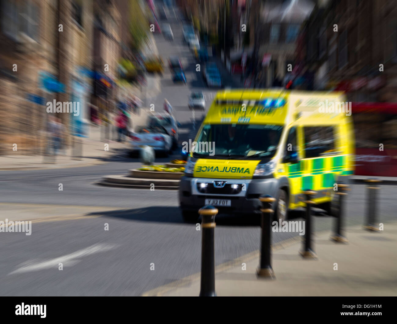NHS Emergency Ambulance rushing through a British town centre with motion blur - Stock Image
