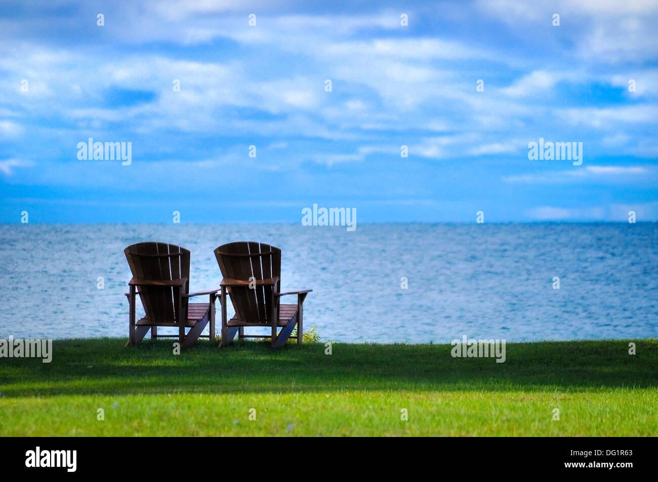 two Adirondack chairs on the shore of Lake Ontario New York usa - Stock Image