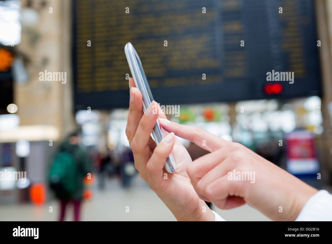 Woman using her mobile phone in hall trainstation. Close up hands - Stock Image