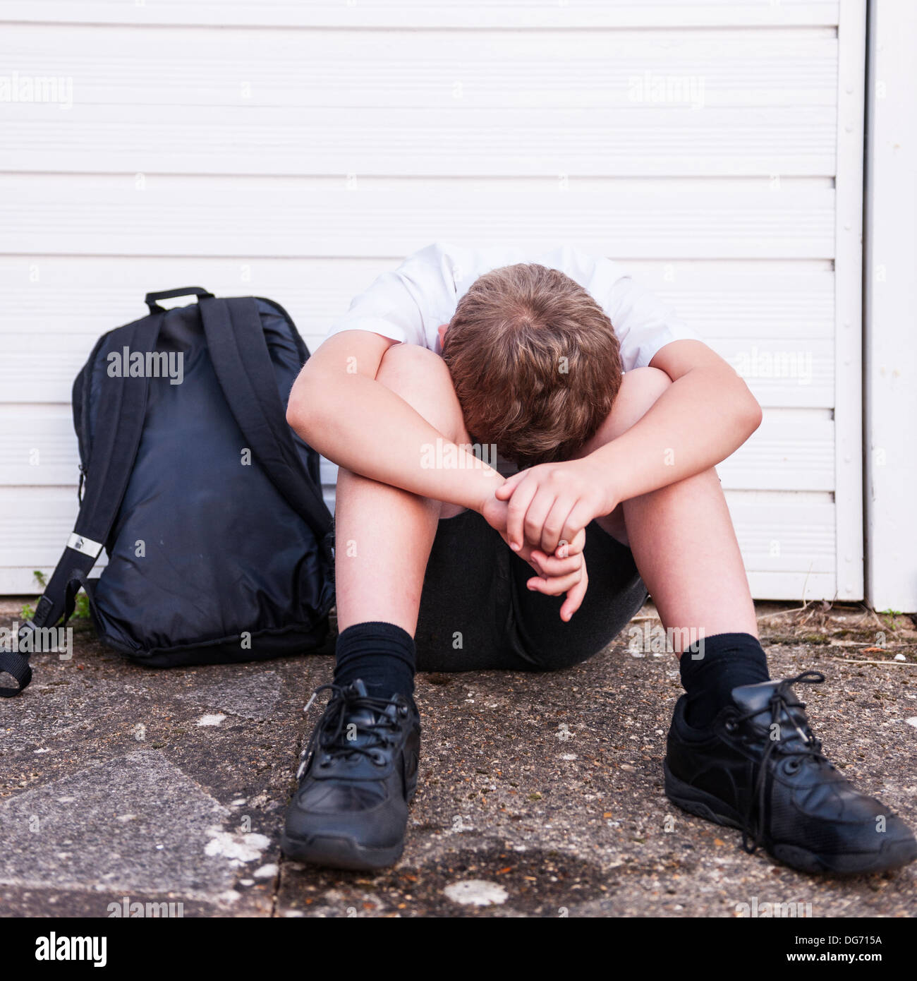 A boy of 10 looking sad and depressed in his school uniform showing the effects of bullying in the UkStock Photo