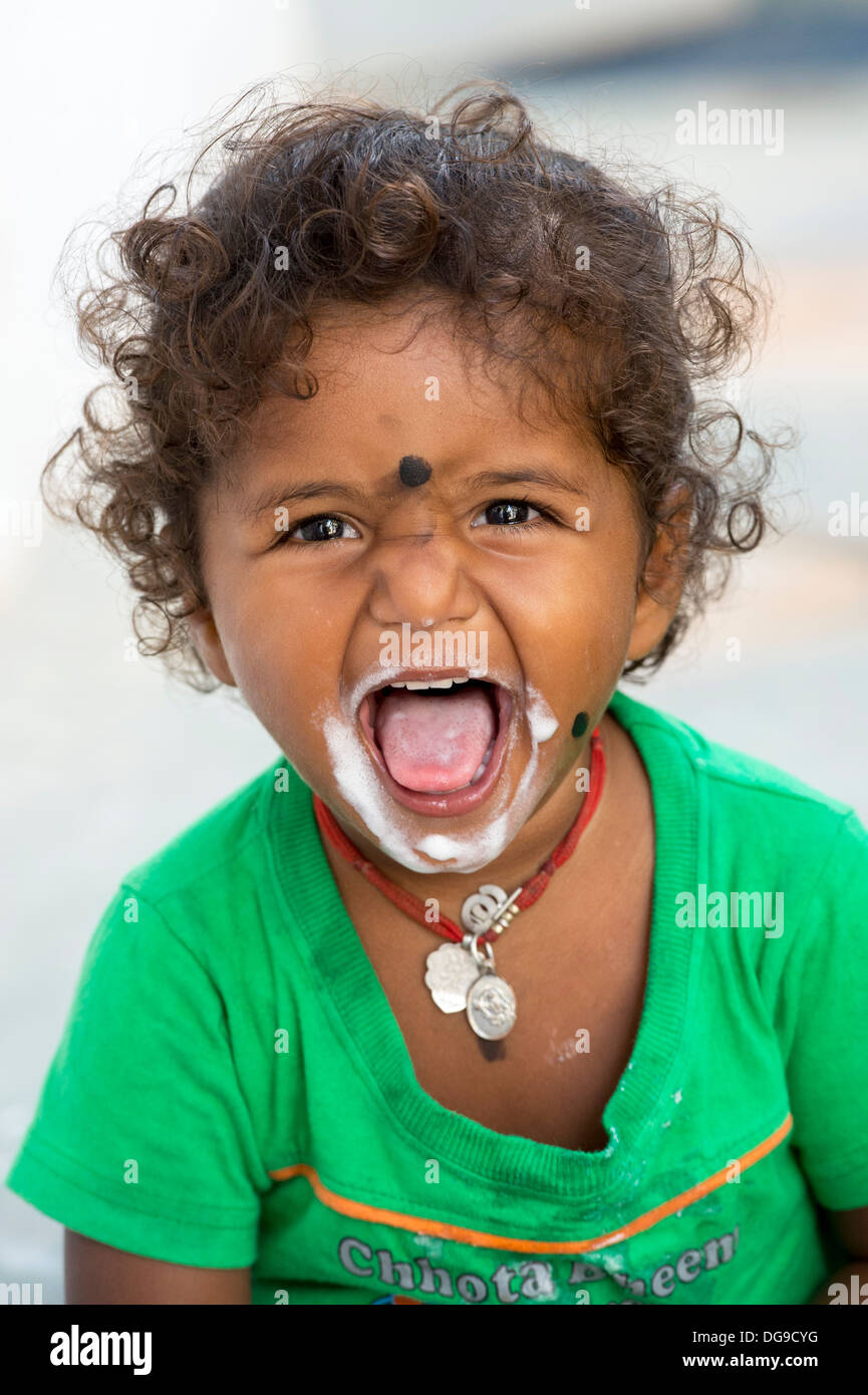 Young Indian girl / infant eating ice cream in a rural indian village. Andhra Pradesh, India - Stock Image