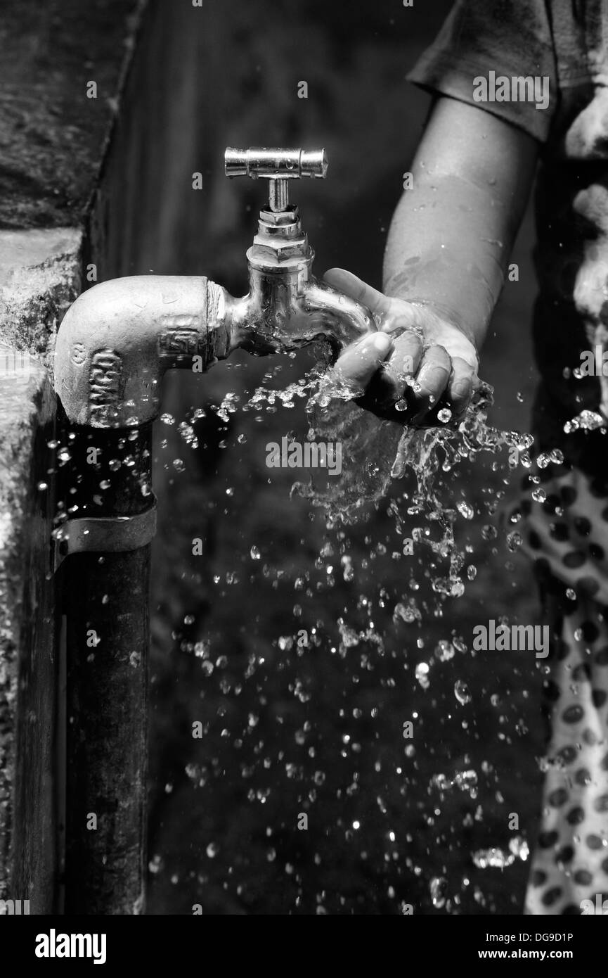 Young Indian girl / infant playing with water from a tap in a rural Indian village. Andhra Pradesh, India. Black - Stock Image
