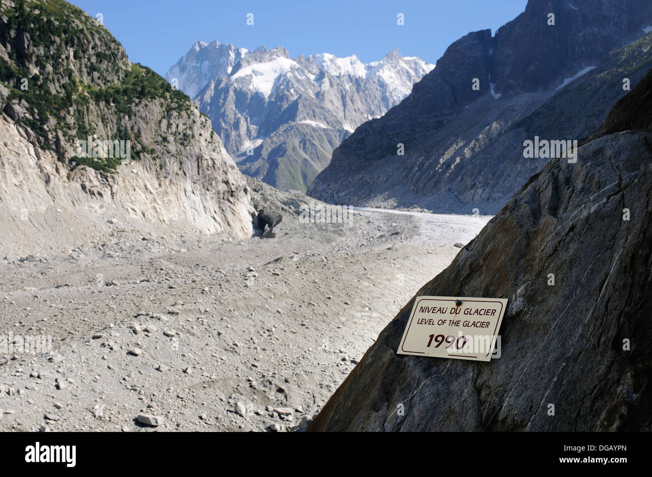 A sign showing the extent of glacial retreat recently - the Mer de Glace now far below the sign showing the level Stock Photo