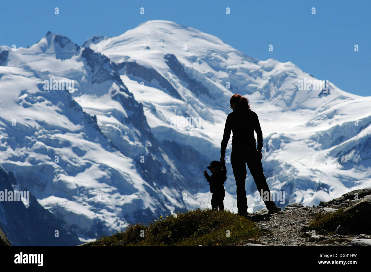 Mother and son at lac Blanc silhouetted against Mont Blanc, Chamonix, France Stock Photo