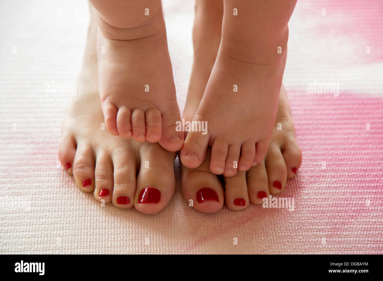 Baby toes on her mother's feet - Stock Image