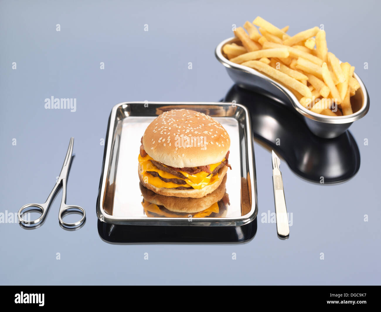 Burger and fries sitting in surgical trays illustrating unhealthy diet - Stock Image