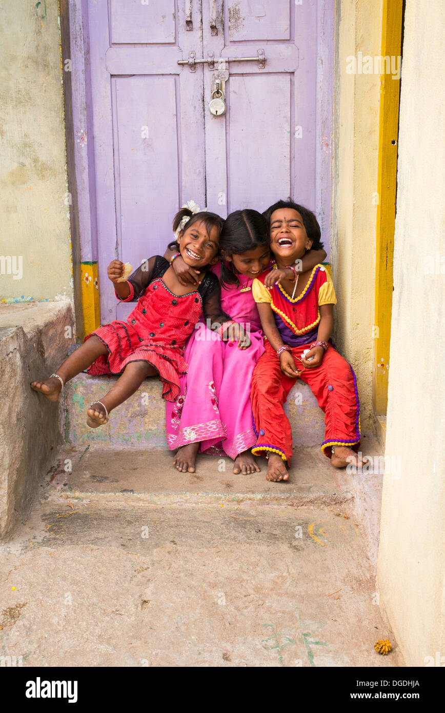 Smiling happy young rural Indian village girls sitting laughing in front of their village house. Andhra Pradesh, - Stock Image