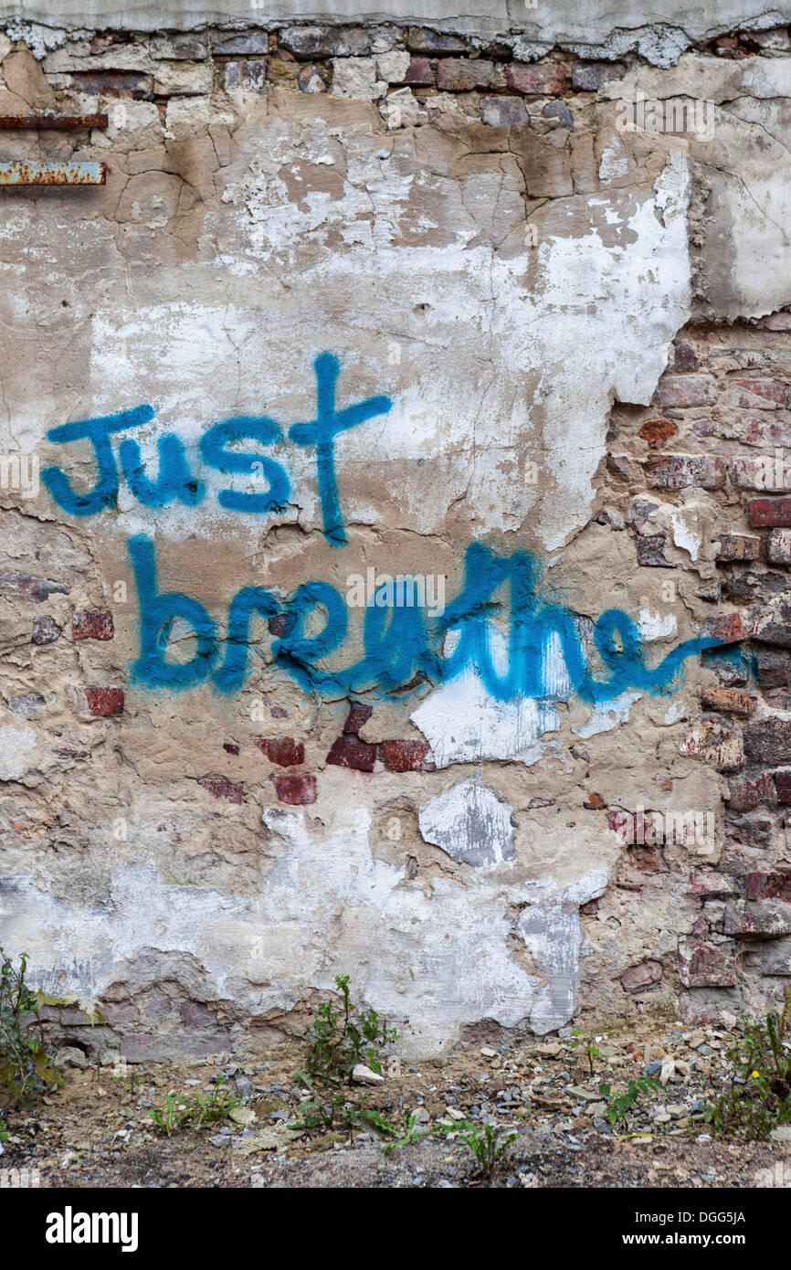 'Just breathe' graffiti advice on a decaying, derelict wall with exposed brick and crumbling plaster in - Stock Image