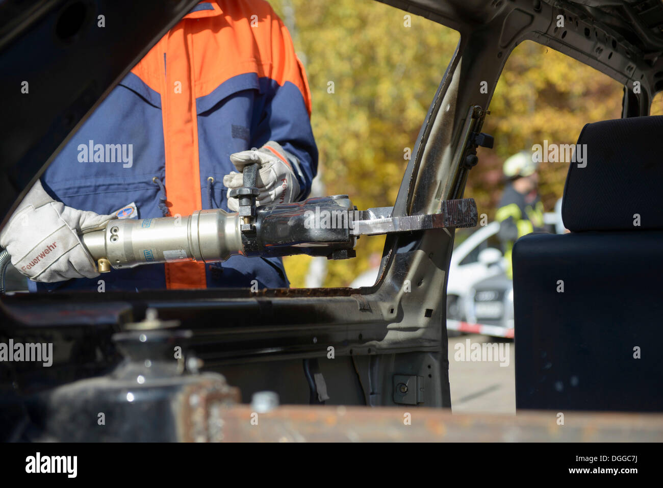 Firefighter working with hydraulic rescue equipment, final fire service drill of the young Stuttgart firefighters - Stock Image
