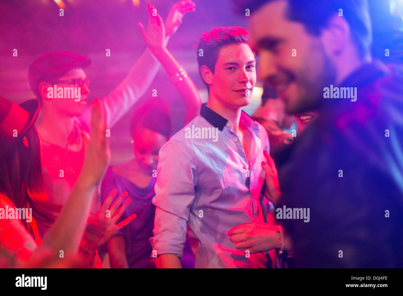 Teenage boy surrounded by group of people dancing at party - Stock Image