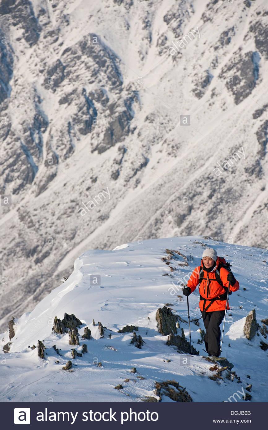 Female climber walking up snow covered ridge - Stock Image
