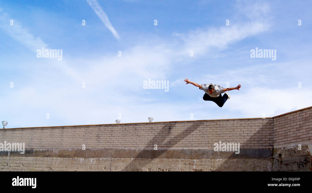 A parkour athlete mid flight. - Stock Image