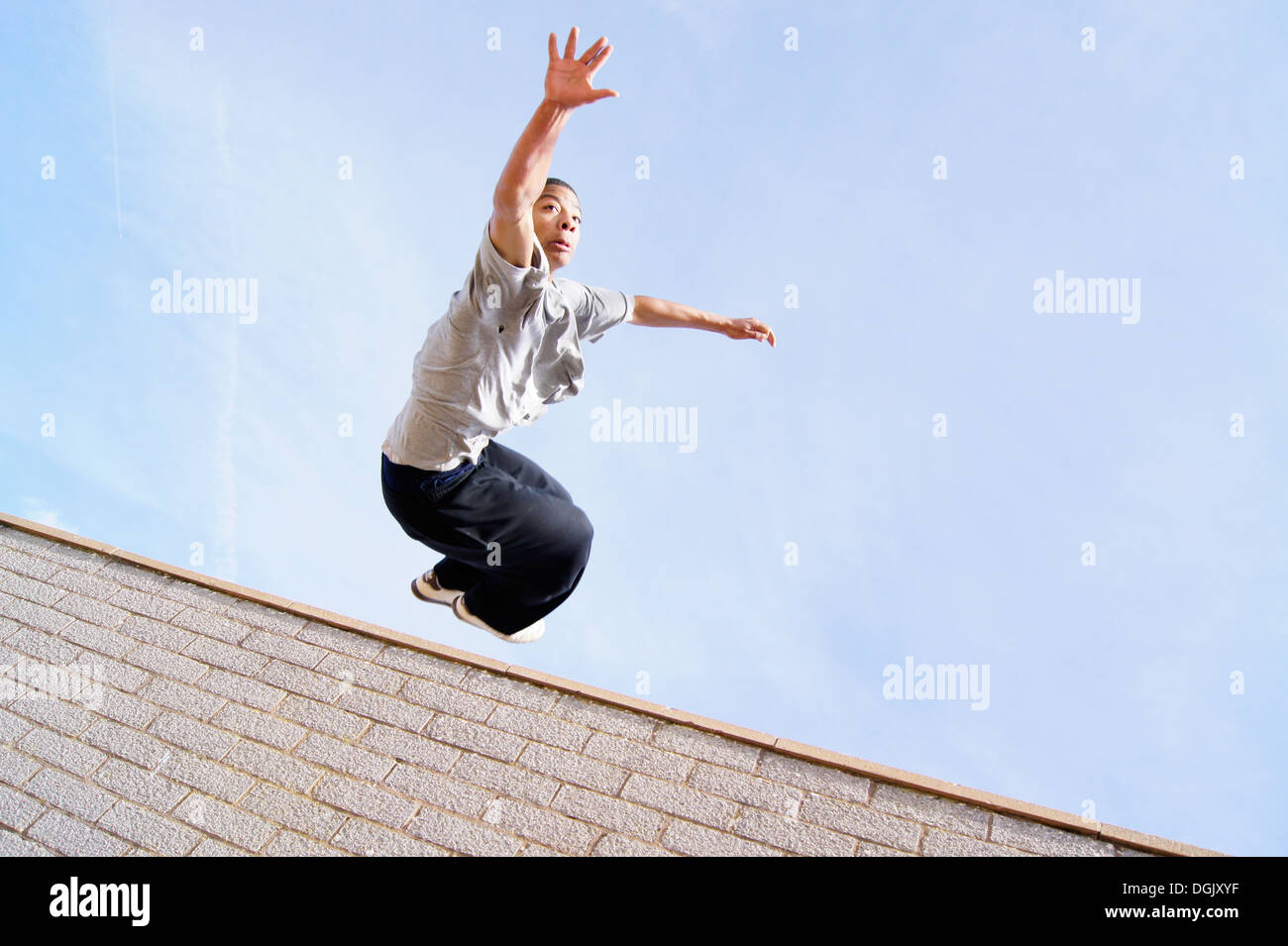 A parkour athlete leaping over a wall. - Stock Image