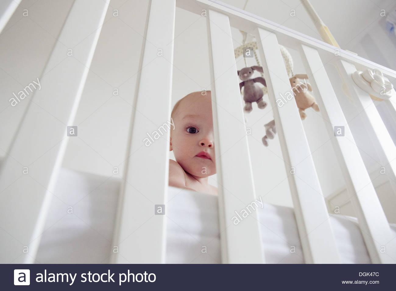 Baby boy behind bars of crib - Stock Image