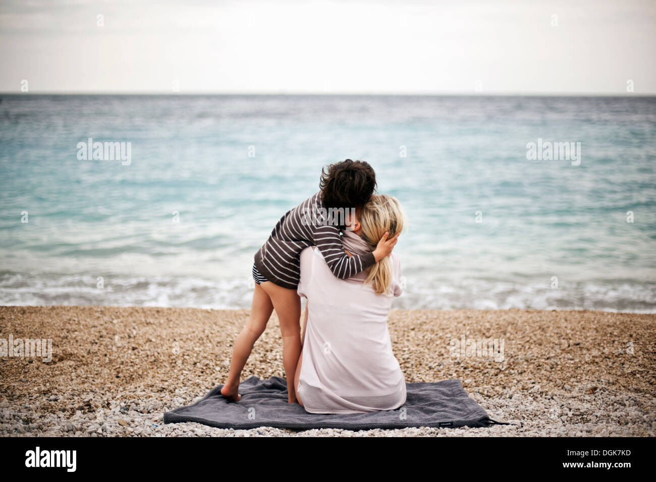Boy hugging mother on a beach, rear view - Stock Image