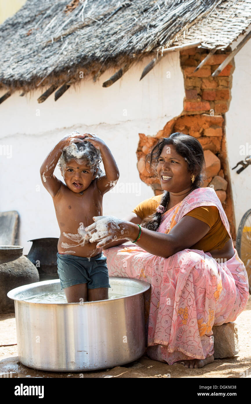 Indian Mother washing her girl in a metal pot in a rural indian village. Andhra Pradesh, India - Stock Image