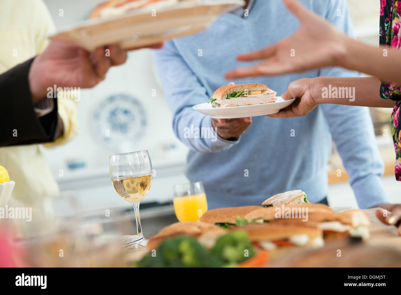 An Informal Office Event People Handing Plates Of Food Across A - Office buffet table