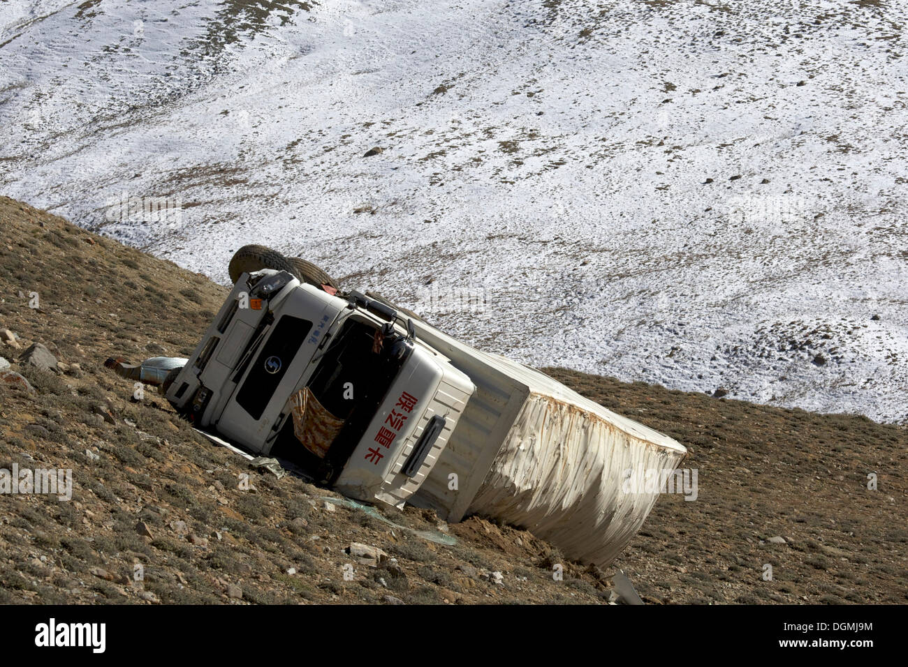 Overturned Chinese truck that crashed off the Pamir Highway on Koitezek Pass, Pamir, Tajikistan, Central Asia, Asia - Stock Image