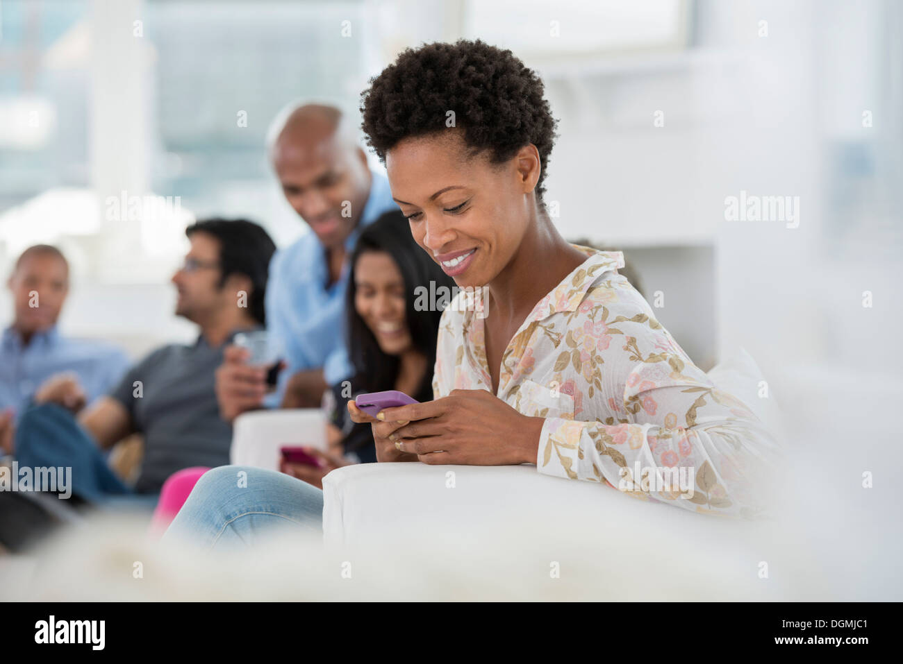 office event. A woman checking her smart phone. - Stock Image