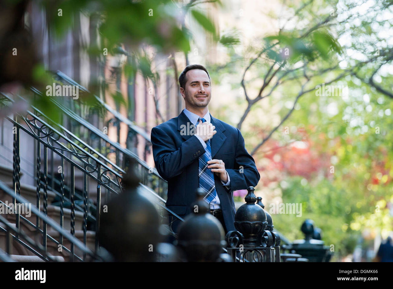 A man in a business suit adjusting his tie. At the bottom of the steps of a townhouse in a terrace. - Stock Image