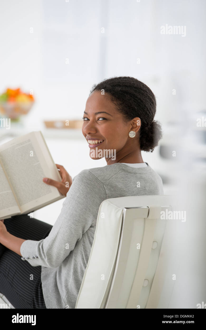 Business. A woman sitting and reading a book. Research or relaxation. Looking over her shoulder and smiling. - Stock Image