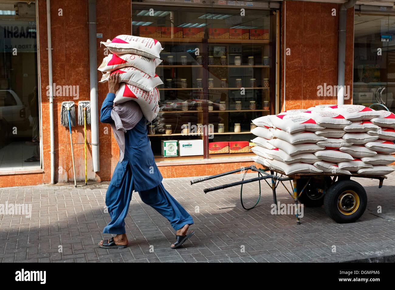 Worker carrying sacks of lentils on his shoulder, Deira, Old Souk, Dubai, United Arab Emirates, Middle East - Stock Image