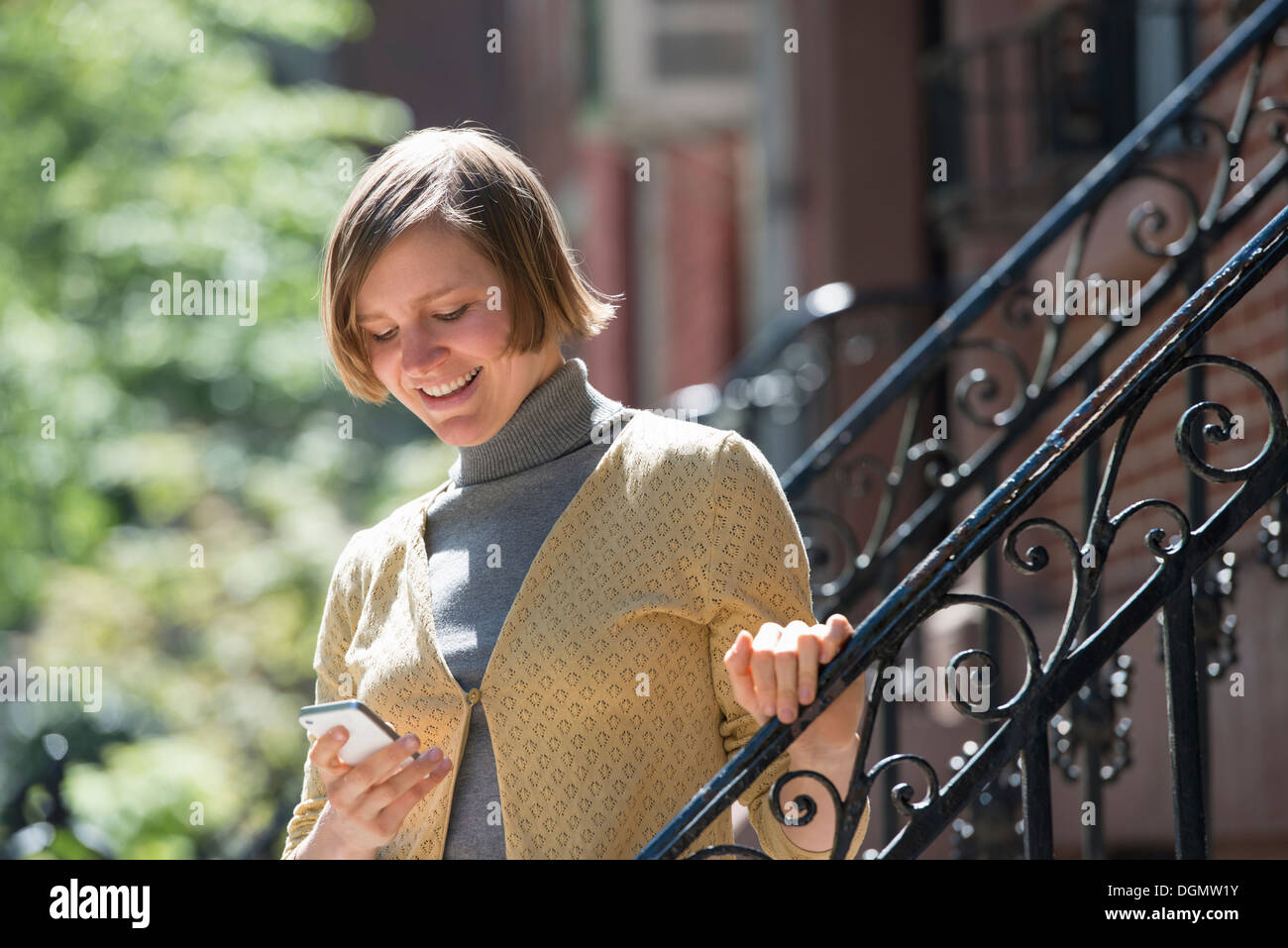 City. A woman on steps outside a townhouse, checking her smart phone. - Stock Image