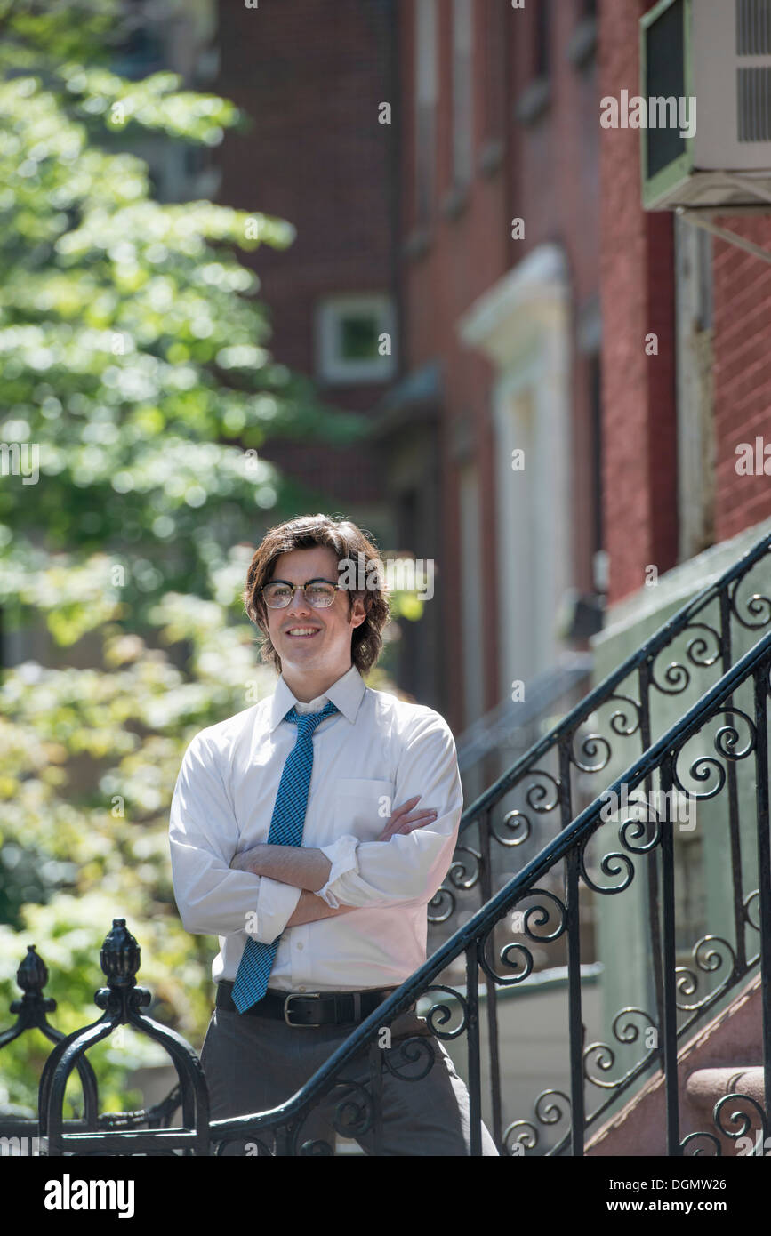 City. A young man in w white shirt and blue tie, standing with arms folded outside a townhouse, on the steps. - Stock Image