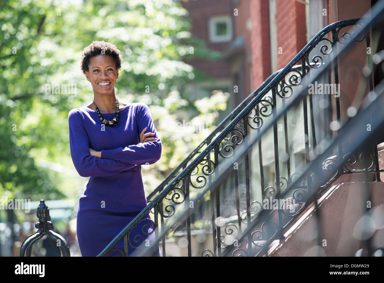 City. A woman wearing a purple dress, standing on the steps outside a townhouse. - Stock Image