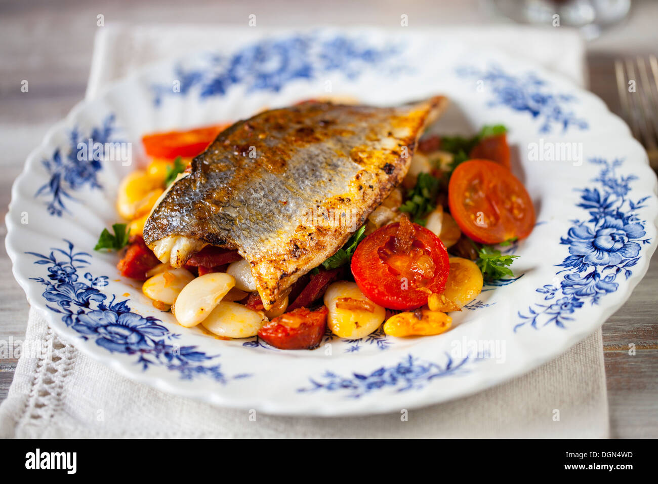 Sea bass with butter bean, tomato and chorizo salad - Stock Image