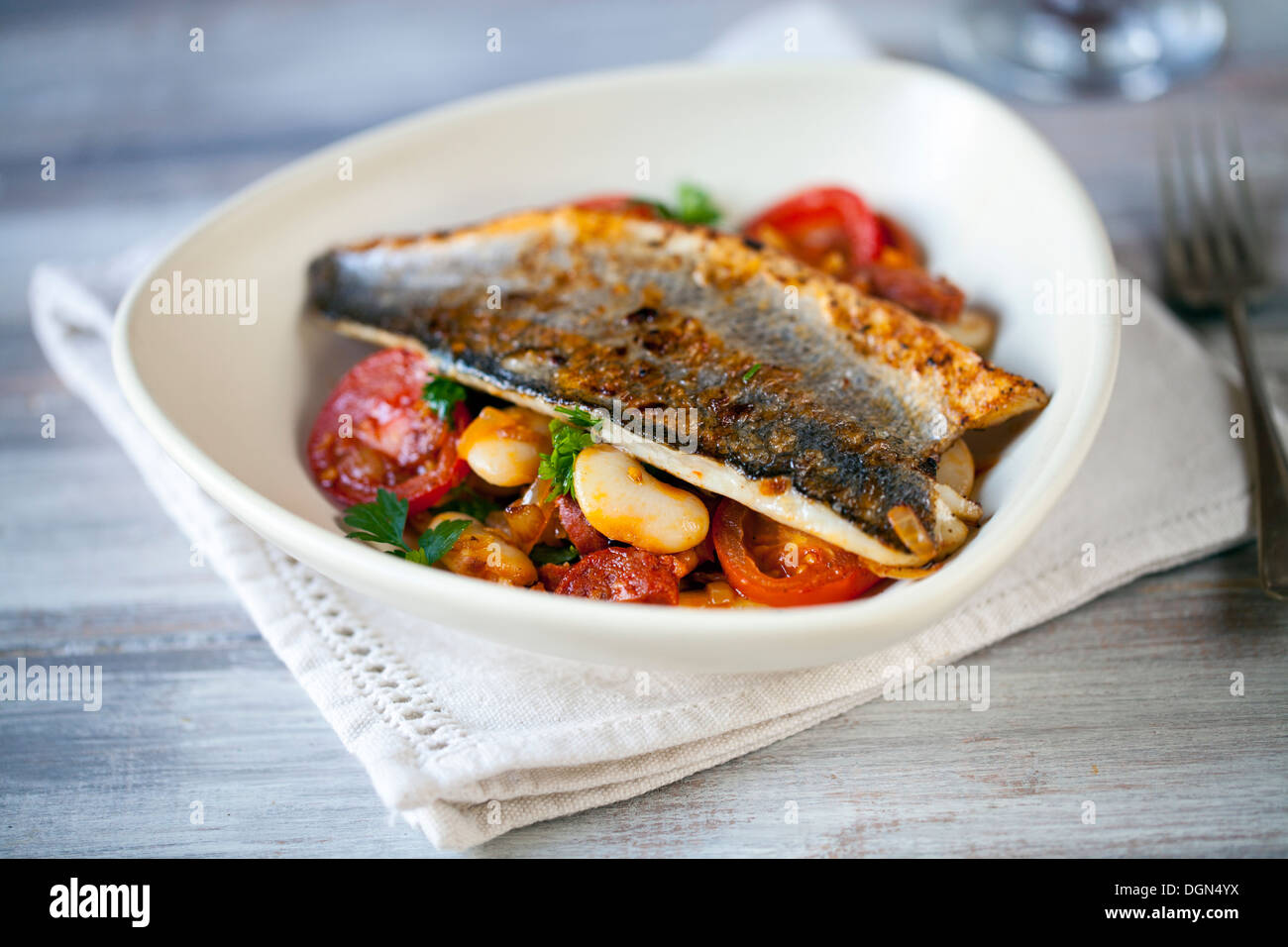 Sea bass fillet with butter bean salad - Stock Image