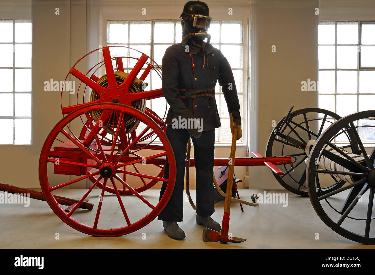 Firefighter wearing a breathing protection mask in front of a hose reel, early 20th century, exhibition of 150 years - Stock Image