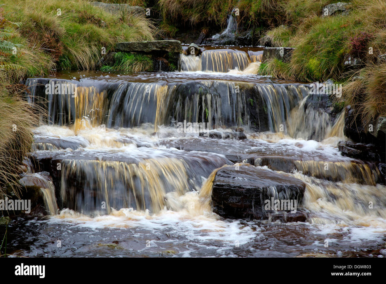Peat stained water cascading down stepped falls in Crowden Brook near Edale in the Derbyshire Peak District - Stock Image