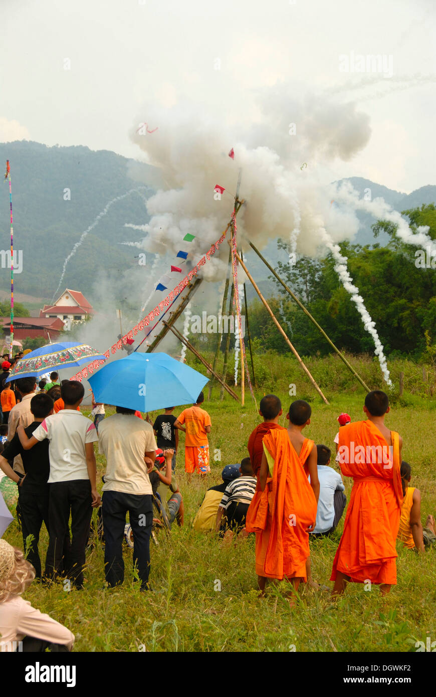 Festival, rocket firing, bang fai, launch and explosion of a rocket on the launch pad, monks in orange robes looking - Stock Image