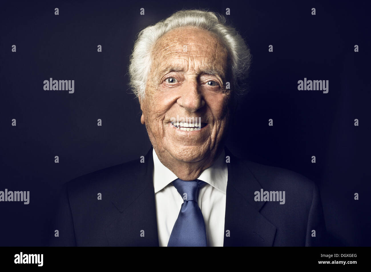 Smiling old man on a black background - Stock Image