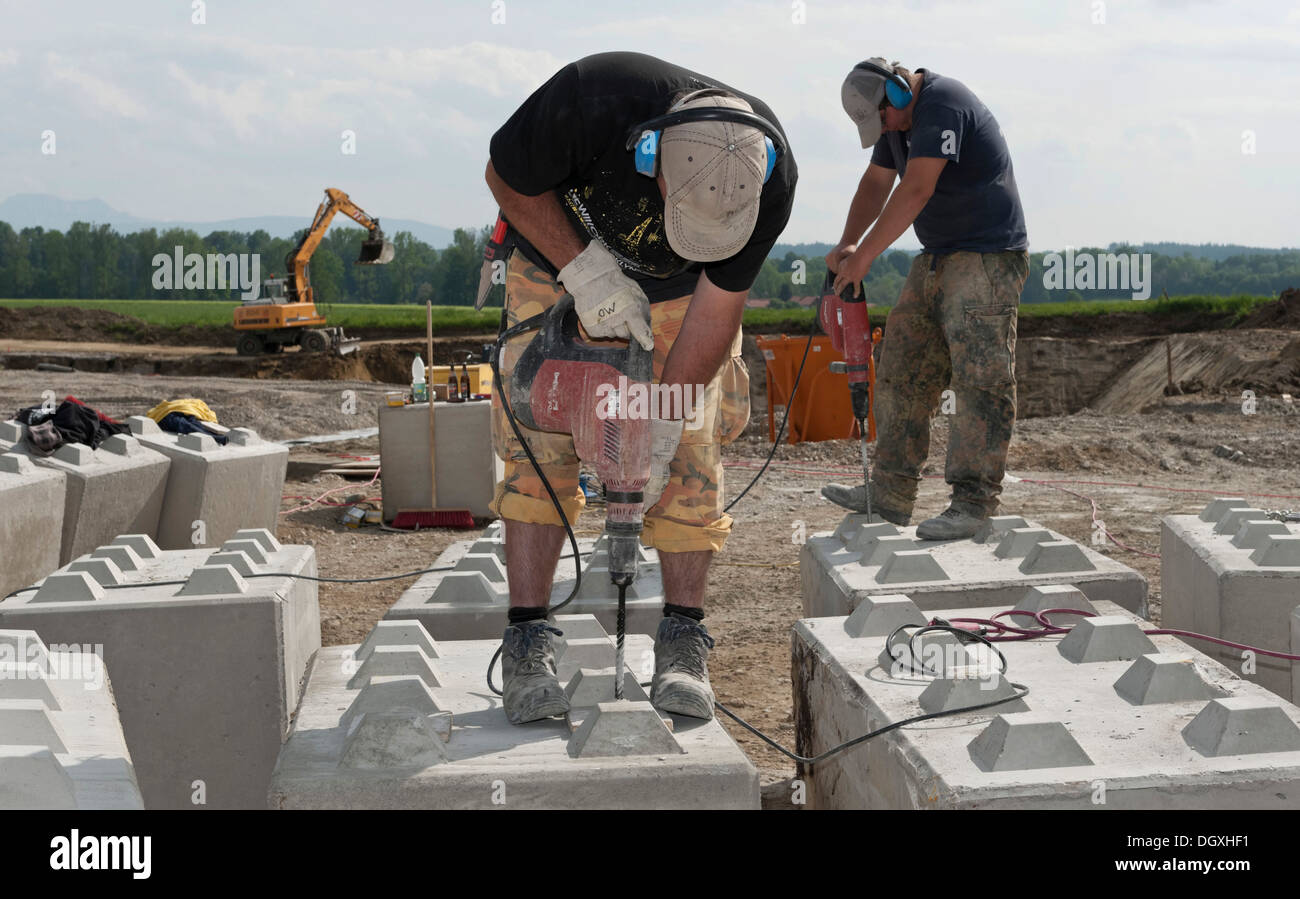 7307fc2f222cc Construction workers drilling holes into concrete blocks during a building  site load test at a construction site in Fridolfing