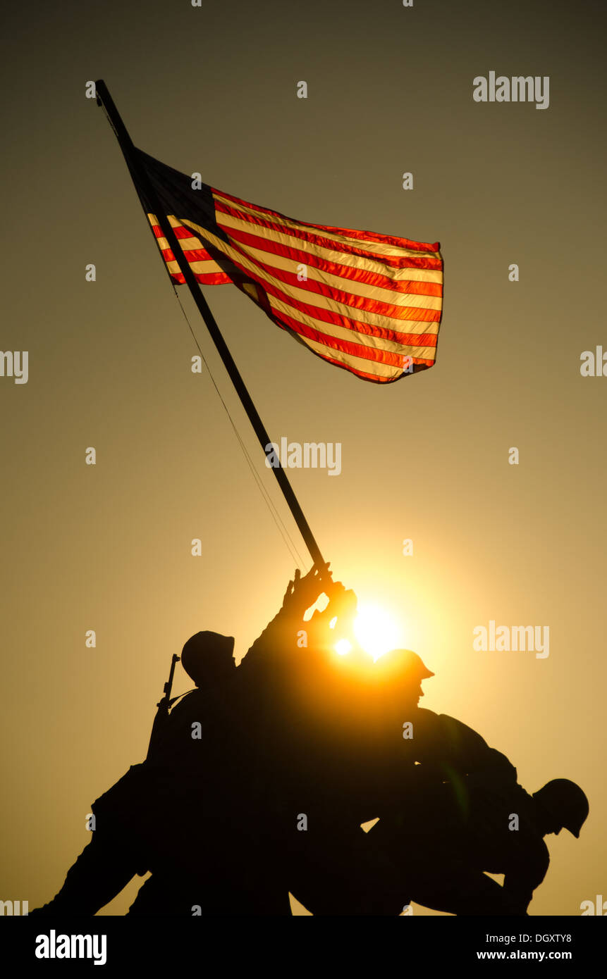 The sun rises behind a silhouette of the Iwo Jima Memorial (US Marine Corps  Memorial) in Arlington, Virginia. The large bronze statue is based on a ...