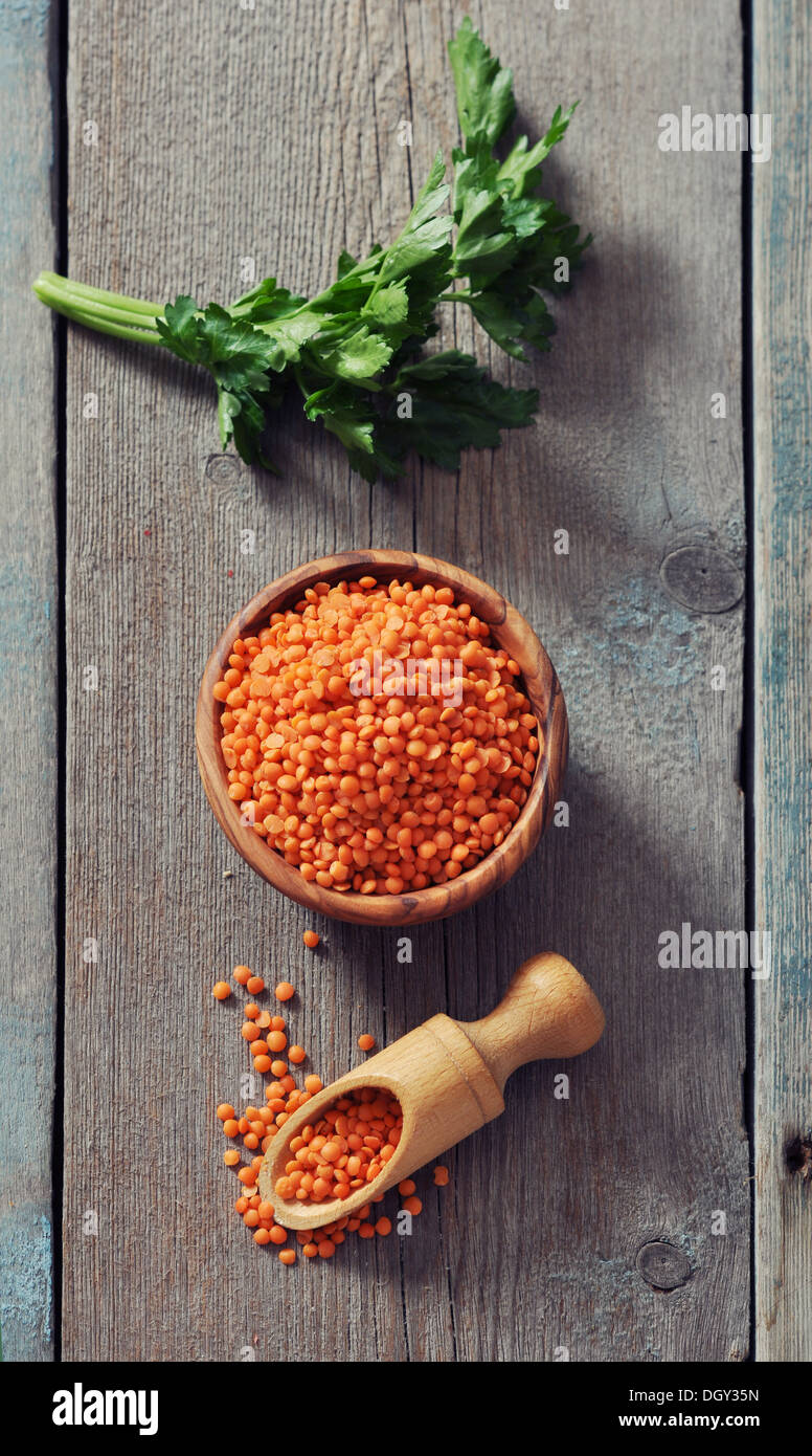 Lentils in wooden bowl with scoop on wooden background  - Stock Image