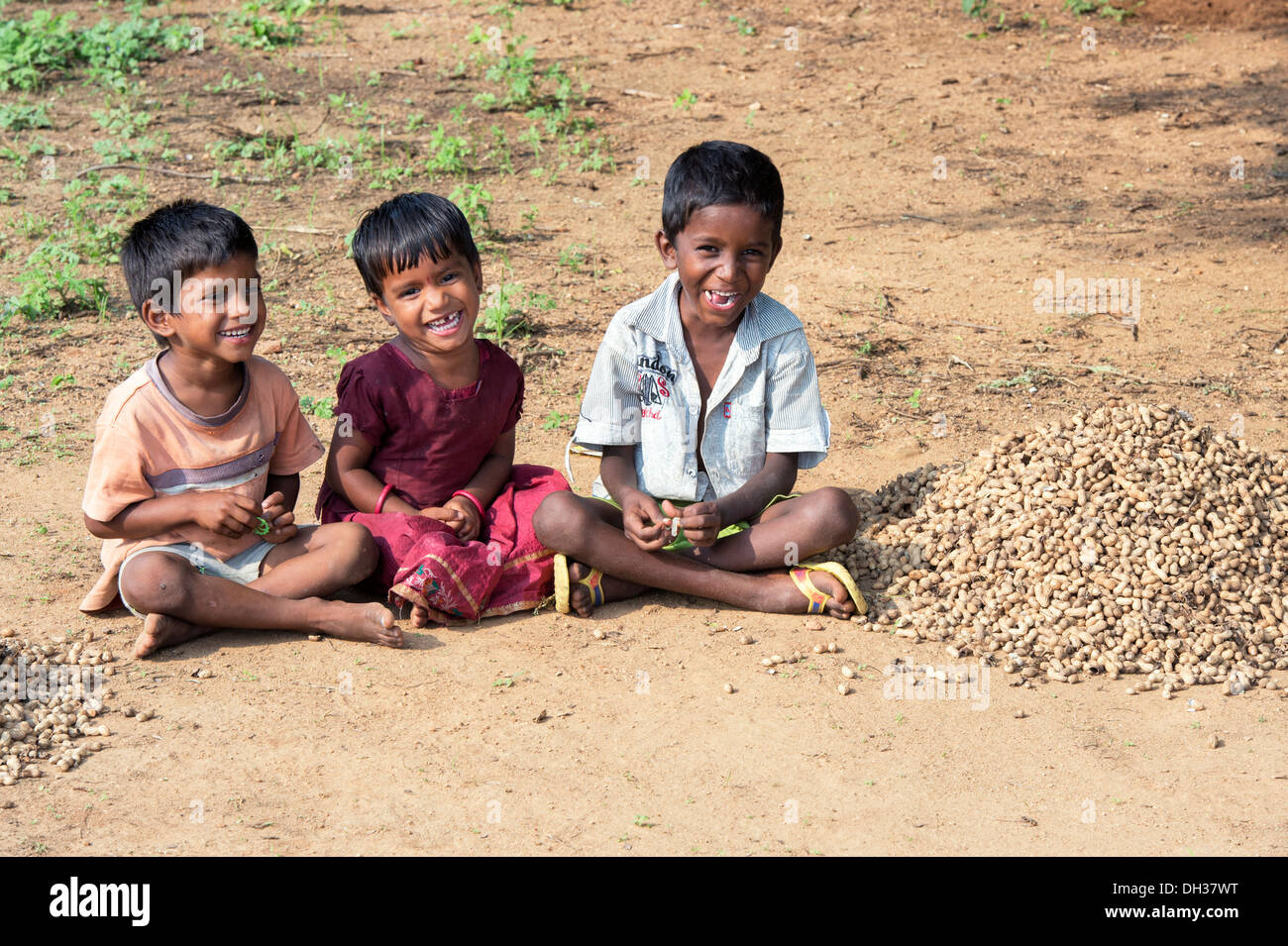 Young Indian village children sitting cross legged on the ground in a rural indian village. Andhra Pradesh, India - Stock Image