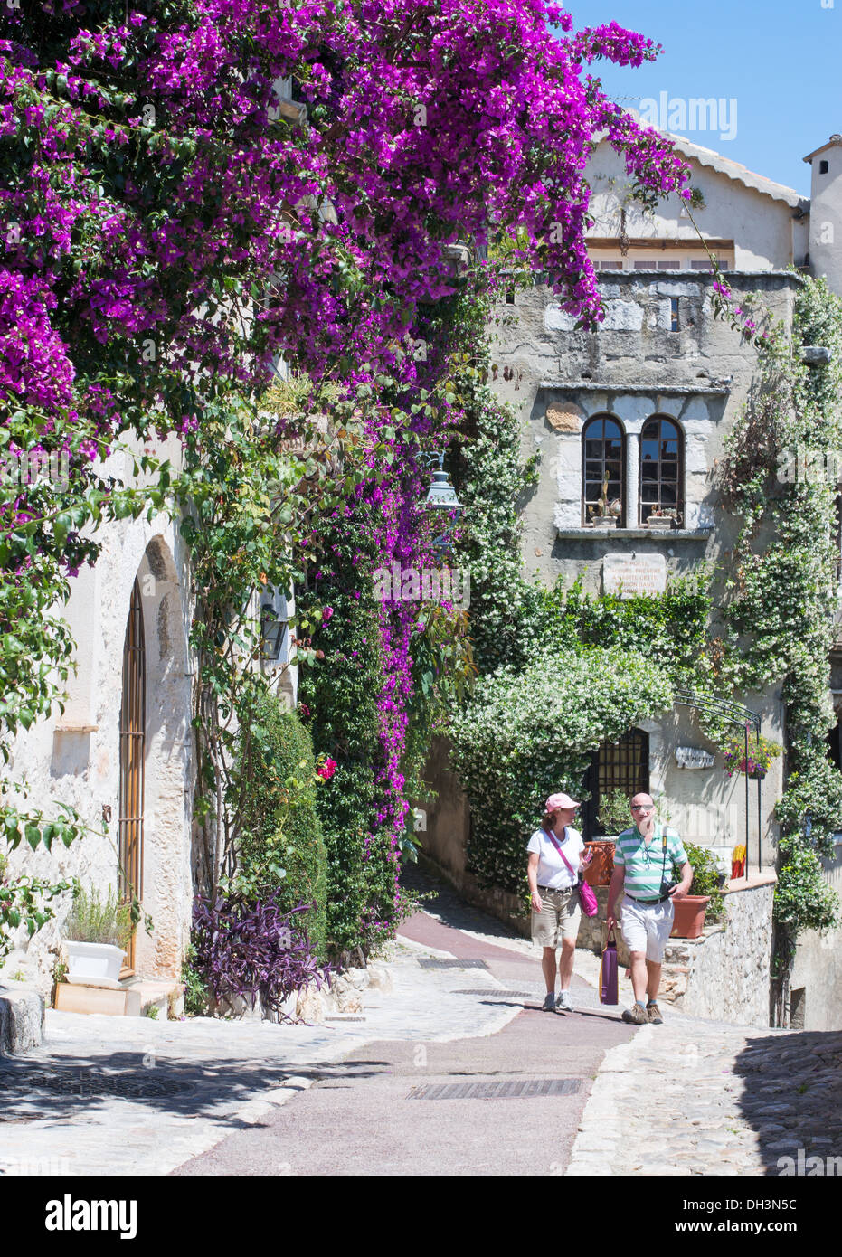 Couple walking past bougainvillea in the village of St Paul de Vence, France, Europe Stock Photo