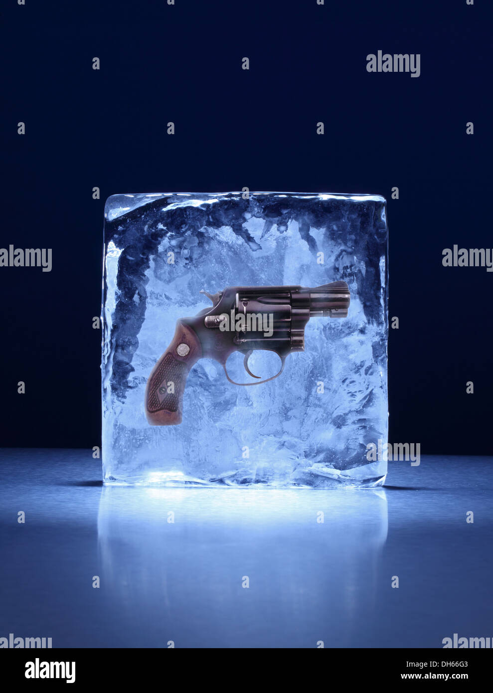 A handgun frozen in a clear block of ice - Stock Image