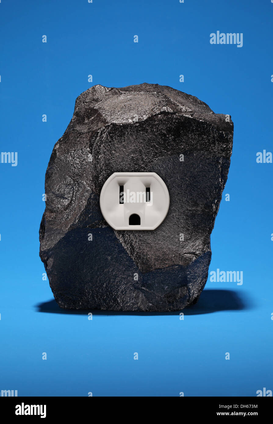 A large piece of black coal with a single electrical outlet. Bright blue background - Stock Image