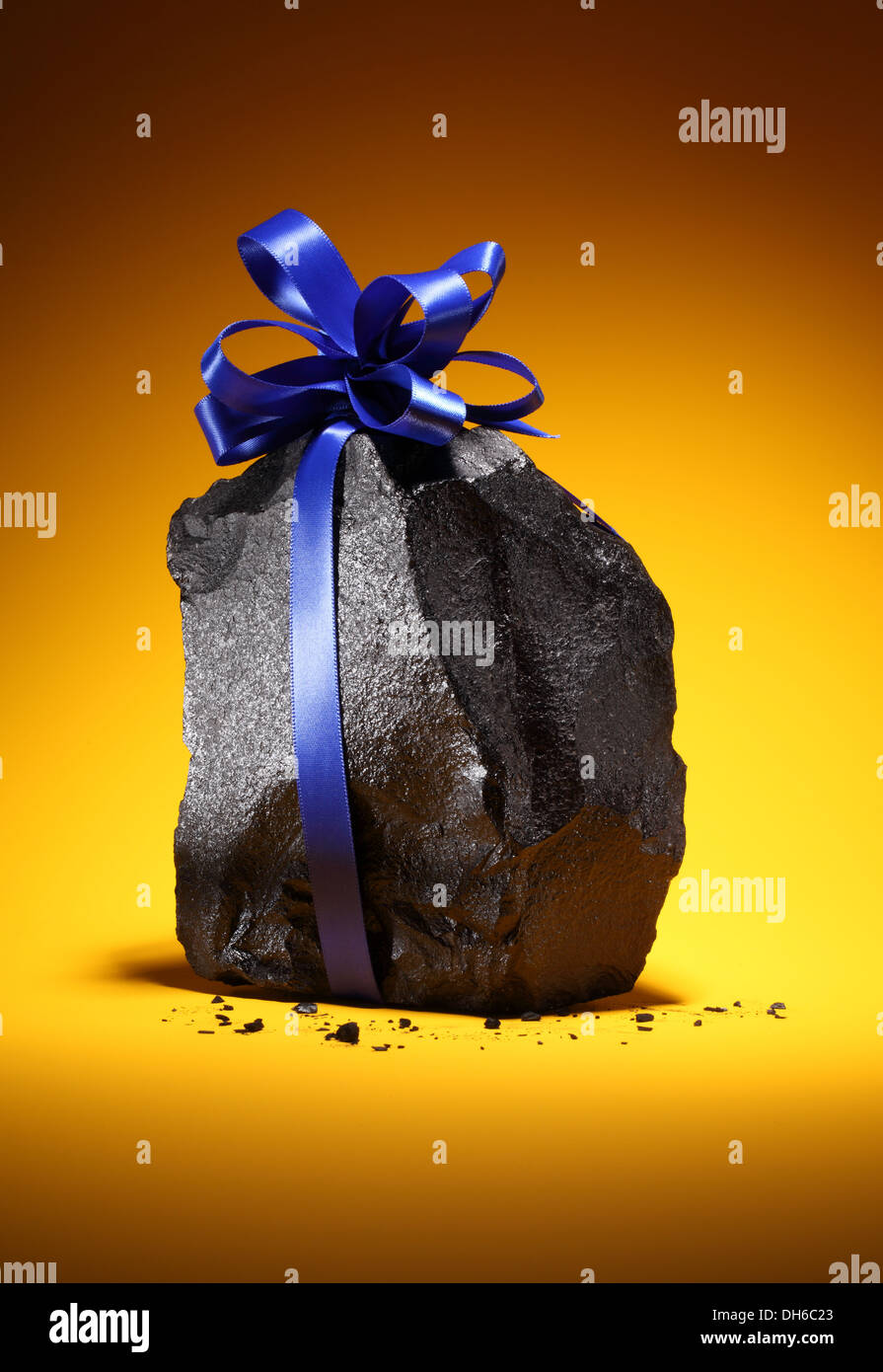 A black black chunk of coal with a blue ribbon tied around it. Bright orange background. - Stock Image